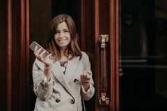 Elegant gorgeous lady in raincoat, holds mobile phone, waits for call, poses outdoor near doors, going for work, feels pleased, up stock images