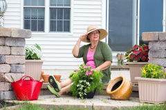 Elegant Grandma posing as she pots up plants. On the steps of her home in terracotta pots to decorate the patio and house Royalty Free Stock Photos