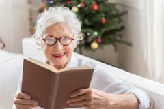 Elegant gray-haired senior lady is reading story Stock Photos