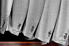 Elegant gray suits in a row inside suit store Stock Photos