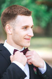 Elegant groom in black costume and purpure bow-tie outdoor royalty free stock images