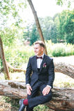 Elegant groom in black costume and purpure bow-tie outdoor stock image
