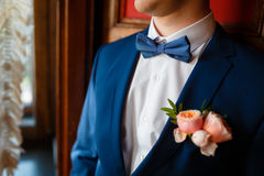Elegant groom in blue suit. Straightens his tie in an expensive hotel, going to a meeting royalty free stock image