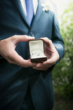 Elegant groom holding open box with wedding rings Stock Photos