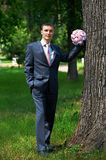 Elegant groom standing about tree Royalty Free Stock Photography