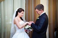 Elegant groom wears a wedding ring a happy bride stock image