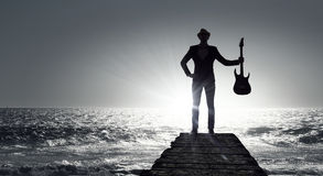 Elegant guitarist silhouette . Mixed media Stock Photo