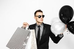 An elegant guy in a black suit and sunglasses, with shopping bag stock image