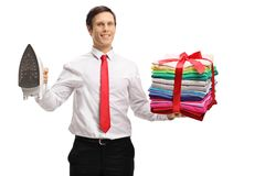 Elegant guy holding an iron and a stack of ironed and packed clo Stock Images