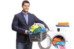 Elegant guy holding a laundry basket filled with clothes in fron Stock Image