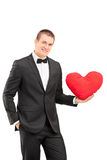 Elegant guy holding a red heart shaped pillow Stock Photos