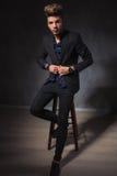 Elegant guy posing seated in dark studio fixing his jacket Stock Image