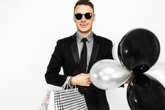 Elegant guy in sunglasses, black suit, holding bags, for shopping, and black balloons, on white background. Black Friday shopping, royalty free stock images