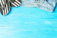 Elegant häftklammermatarejeans för ram på blå träbakgrund, copyspace för text, sommarsemester royaltyfri bild