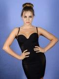 Elegant härlig flicka i svart åtsmitande posera för klänning Arkivbilder