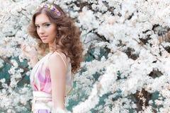 Elegant härlig flicka med frodigt hår med en kant av ljust färgade blommor i en trädgård nära morgon för vår för blomningträd en  Royaltyfri Bild