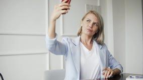 Elegant härlig kvinna som gör selfies på smartphonen i restaurangkafé, kvinnlig med perfekt hud och innegrej stock video