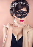 Elegant hairstyle. Beautiful Girl in black veil mask. Masquerade. Makeup. Hairstyle. Jewelry stock photography