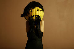 Elegant halloween phantom. Sexy lady with big pumpkin on head. Surrealstic portrait Stock Images