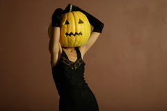 Elegant halloween phantom. Sexy lady with big pumpkin on head. Surrealstic portrait Royalty Free Stock Photography