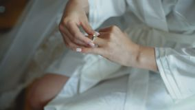 Elegant hand of bride putting silver ring with gemstone on her finger stock video