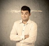 Fast creative sales guy with smoking bullet. An elegant handsome business guy standing in front of wall with a bullet going through his head, making facial Stock Image