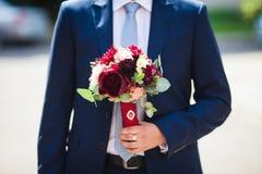 Elegant handsome groom in blue suit with wedding bouquet.  Stock Photo