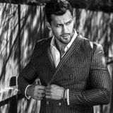 Elegant handsome man in classical grey suit poses near wooden fence Royalty Free Stock Photography