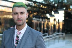 Elegant handsome man with green hair in office space.  Royalty Free Stock Photos