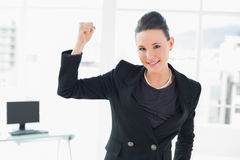 Elegant and happy businesswoman clenching fist in office Royalty Free Stock Photo
