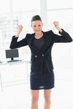 Elegant and happy businesswoman clenching fists in office Stock Photos