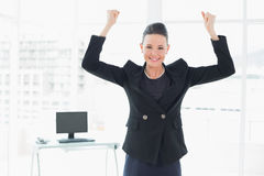 Elegant and happy businesswoman clenching fists in office Stock Image