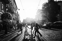 Elegant happy wedding couple running and laughing in sunlight in. City streets at evening in european town. luxury bride and groom having fun. romantic sensual Stock Photo