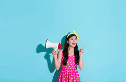Happy woman holding megaphone in blue background. Elegant happy woman holding megaphone in blue background and pointing empty area thinking good idea with cute Royalty Free Stock Images