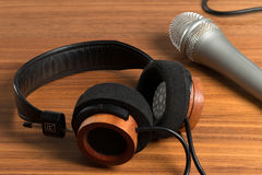 Elegant headphones and a studio microphone on a wooden table Royalty Free Stock Image
