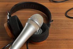Elegant headphones and a studio microphone on a wooden table Royalty Free Stock Photography