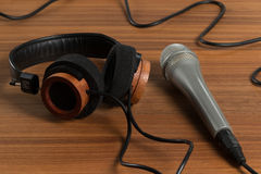 Elegant headphones and a studio microphone on a wooden table Royalty Free Stock Images
