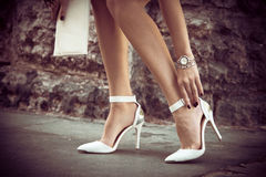 Elegant high heel shoes. Woman legs in elegant white high heel shoes outdoor shot in the city summer day royalty free stock image