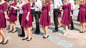 Elegant high school graduates in identical marsala dresses. Elegant high school graduates in the same dresses of marsala dance a waltz in the schoolyard stock photography