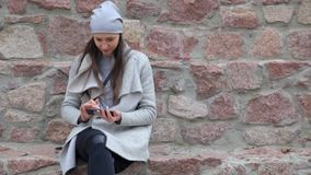Elegant hipster woman texting on smartphone in the city. Stone wall background stock footage