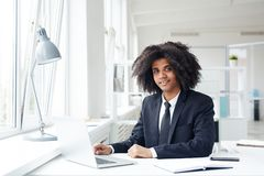 Analyst by workplace. Elegant hispanic businessman with wavy hair sitting in front of laptop and analyzing online data stock photo
