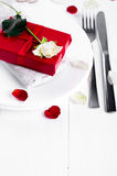 Elegant holiday table setting with red ribbon gift Stock Images