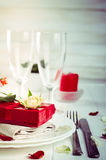 Elegant holiday table setting with red ribbon gift Royalty Free Stock Photography