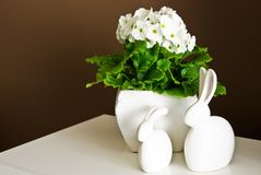 White ceramic easter bunnies home decoration. An elegant home still life composition of two white ceramic easter bunnies and potted flowers in a clay pot Royalty Free Stock Images