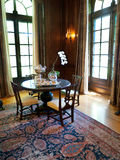Elegant interior. Round table with four chairs in a corner of an opulent interior. Natural light comes in through two French glass doors. Beautiful hand made Stock Images