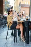 Elegant Italian woman with hat and glasses kisses her cat. An elegant Italian woman, sitting at a bar table, kisses her cat royalty free stock photo