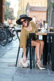 Elegant Italian woman with hat and glasses keeps her cat on a leash. Elegant Italian woman, sitting at a bar table, keeps her cat on a leash stock photos