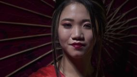 Elegant oriental woman unfolds a red fan with a smile, and covers her face with it, slow motion