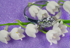 Elegant jewelry and lily of the valley. Elegant jewelry ring with brilliant and spring natural flowers -  lily of the valley Royalty Free Stock Photography
