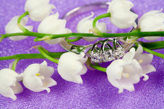 Elegant jewelry and lily of the valley. Elegant jewelry ring with brilliant and spring natural flowers Royalty Free Stock Images